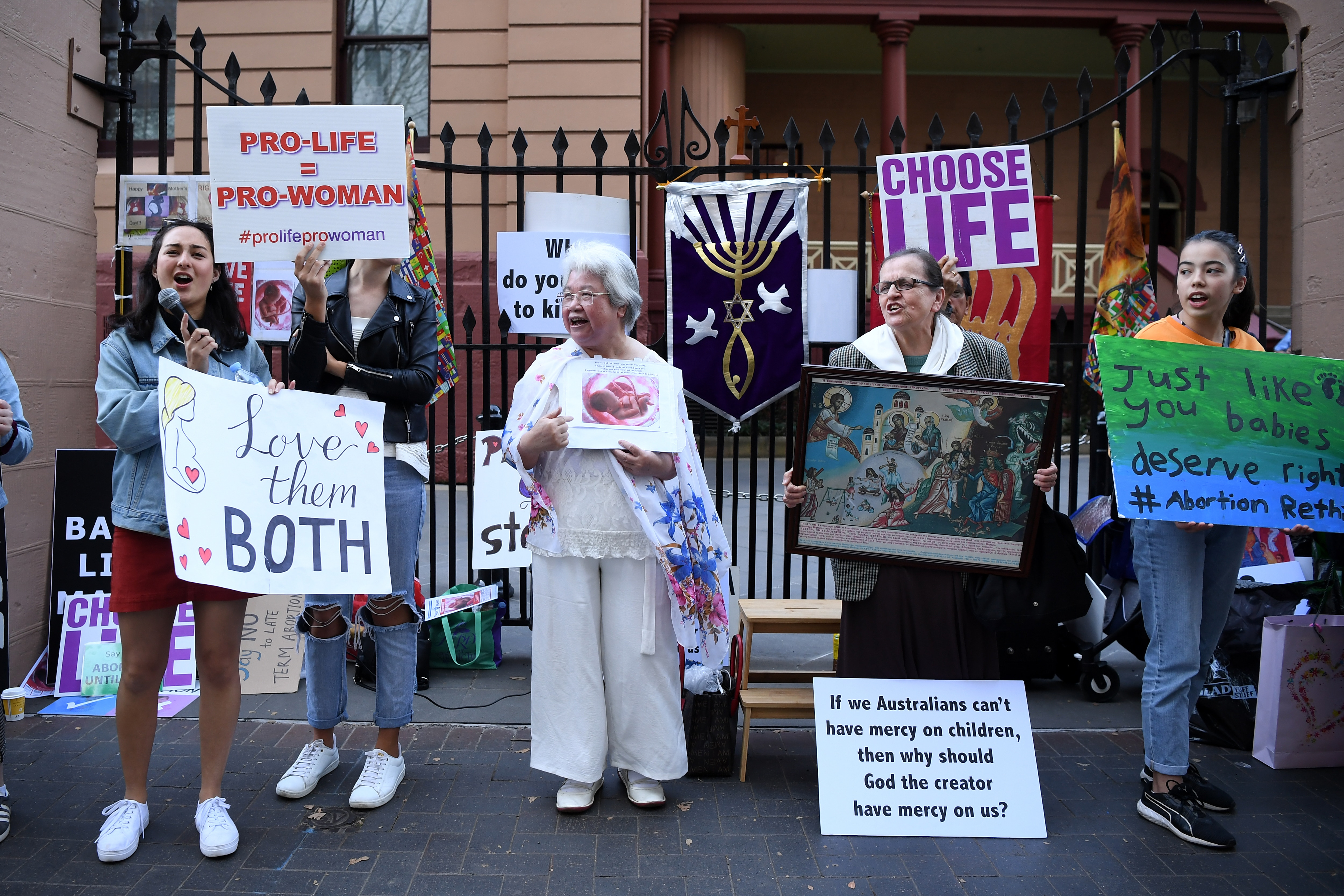 Advocates hold placards during a rally outside the New South Wales Parliament.