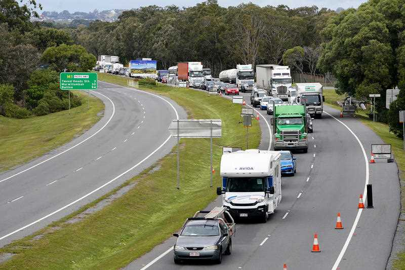 Motorists are seen approaching a checkpoint at Coolangatta on the Queensland- New South Wales border.