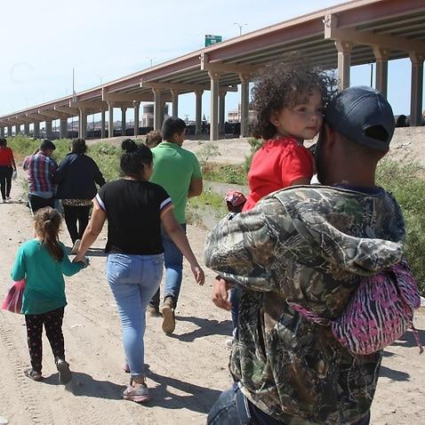 Central American migrants walk into US territory after crossing the Rio Grande under the international bridge in the border city of Ciudad Juarez, Mexico.