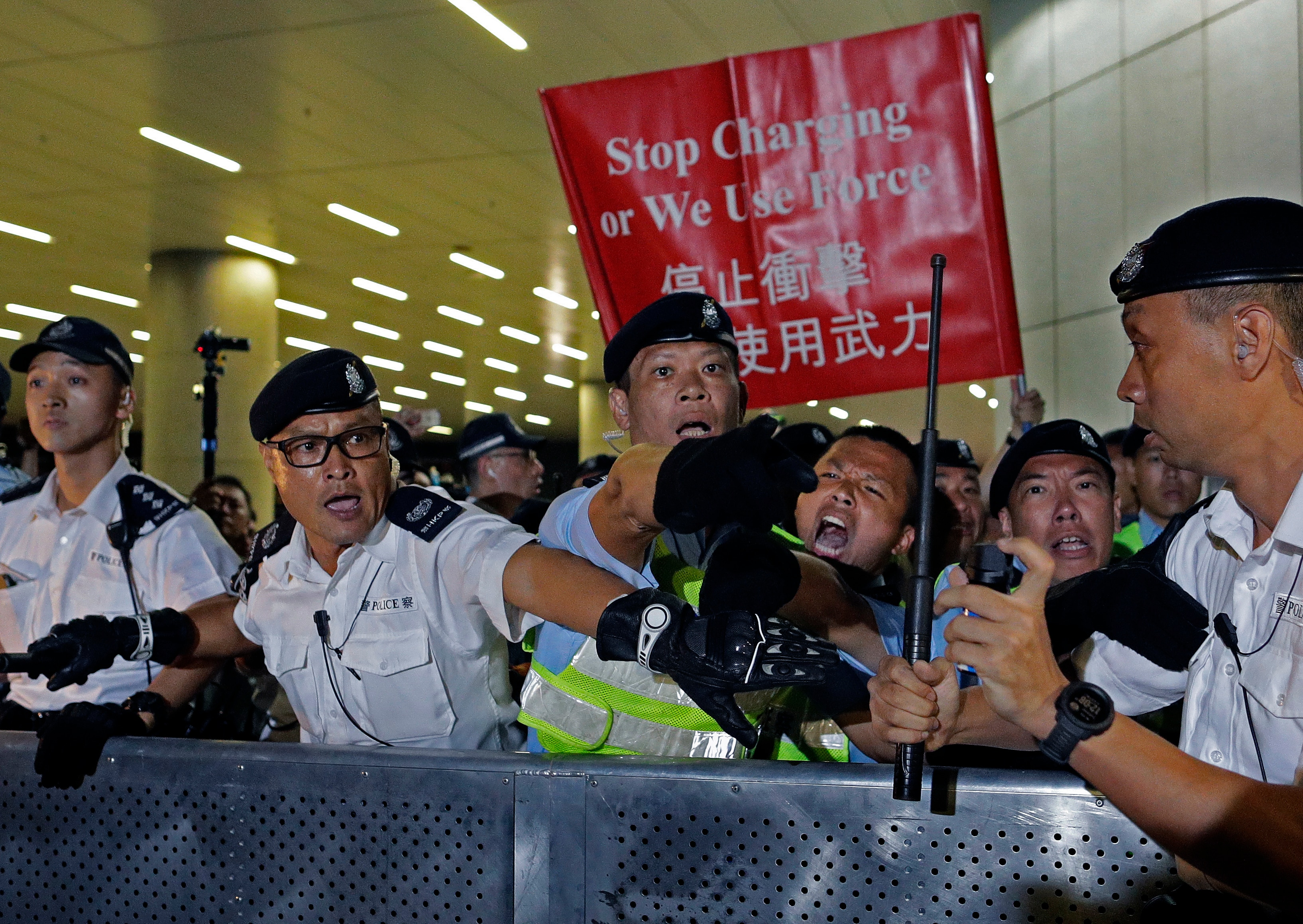 Police officers react as the clash against protesters in a rally against the proposed amendments to the extradition law at the Legislative Council in Hong Kong