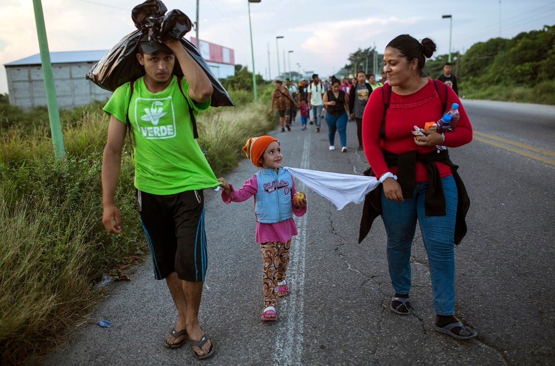 Honduran migrants with their 4-year-old daughter tied to her mother with a piece of cloth so she doesn't get lost in the crowd.