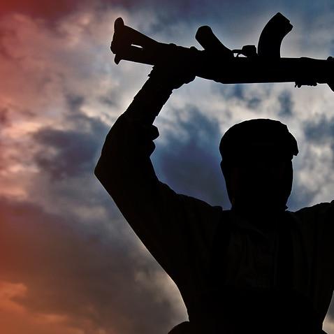 Man holding AK-47 above head