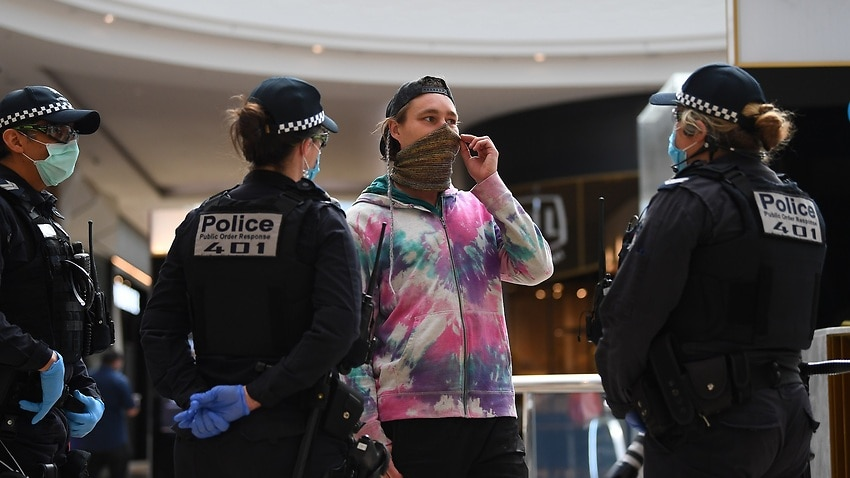 Victoria Police speak to a person inside of Chadstone Shopping Centre following an anti-lockdown protest in Melbourne.