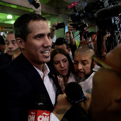 President of the Venezuelan National Assembly, Juan Guaido (C), addresses the media upon his arrival (AAP)
