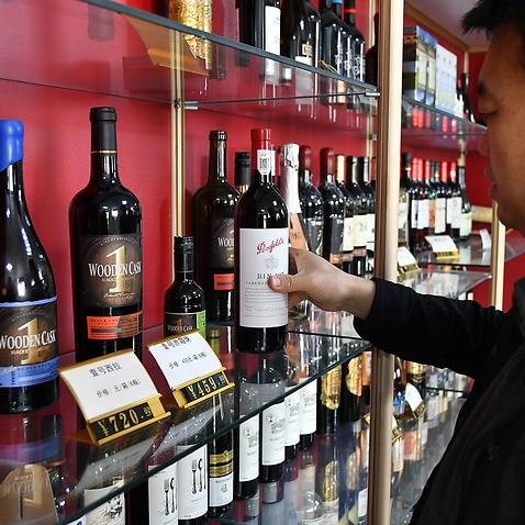 A dealer displays Australian wines at a wholesale department of imported wines in China's Shandong Province on 27 November.