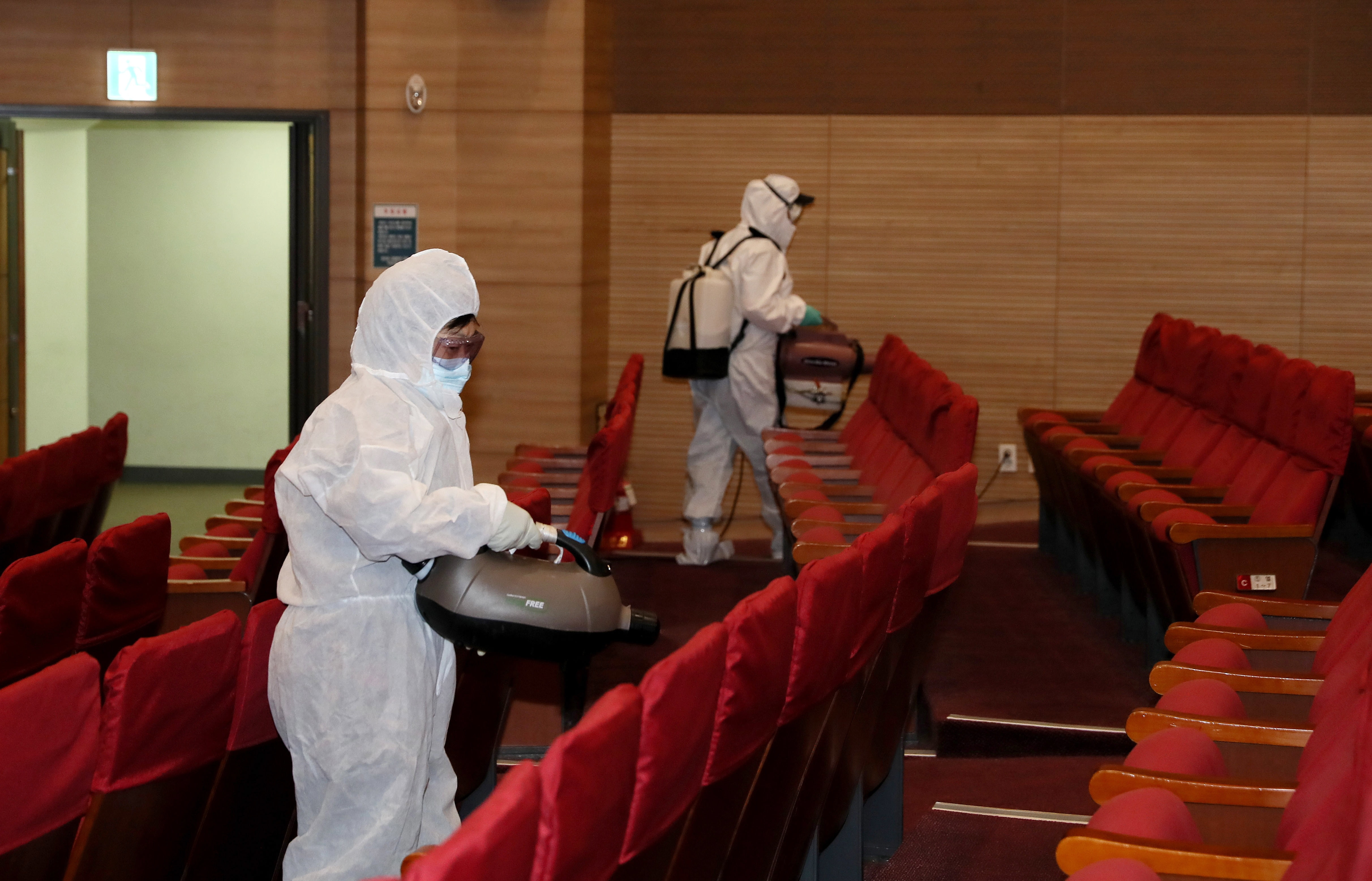 Health workers disinfect the main auditorium at the parliamentary member's office building in the National Assembly in Seoul, South Korea, 24 February 2020.
