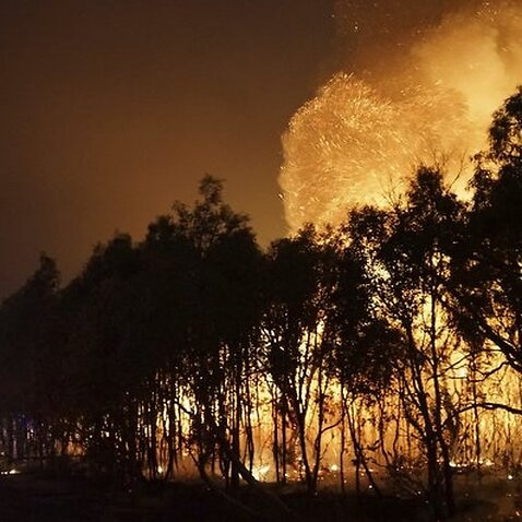 In this photo provided by Costi Farms firefighters, at left, battle a wildfire as it moves through Deepwater National Park in Queensland state, Australia.