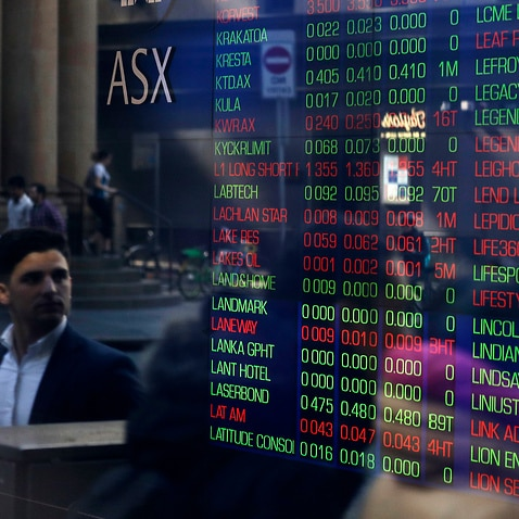 People are reflected in a window as they walk past the Australian Stock Exchange in Sydney, Thursday, Aug. 15, 2019.