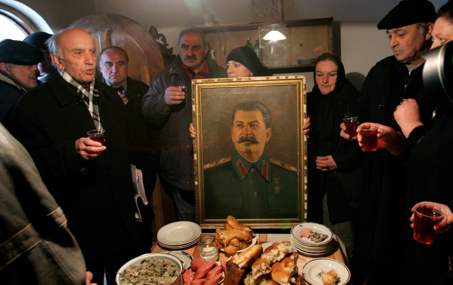 File: People toast, standing around a portrait of Soviet dictator Josef Stalin, after a memorial service at Stalin's hometown of Gori