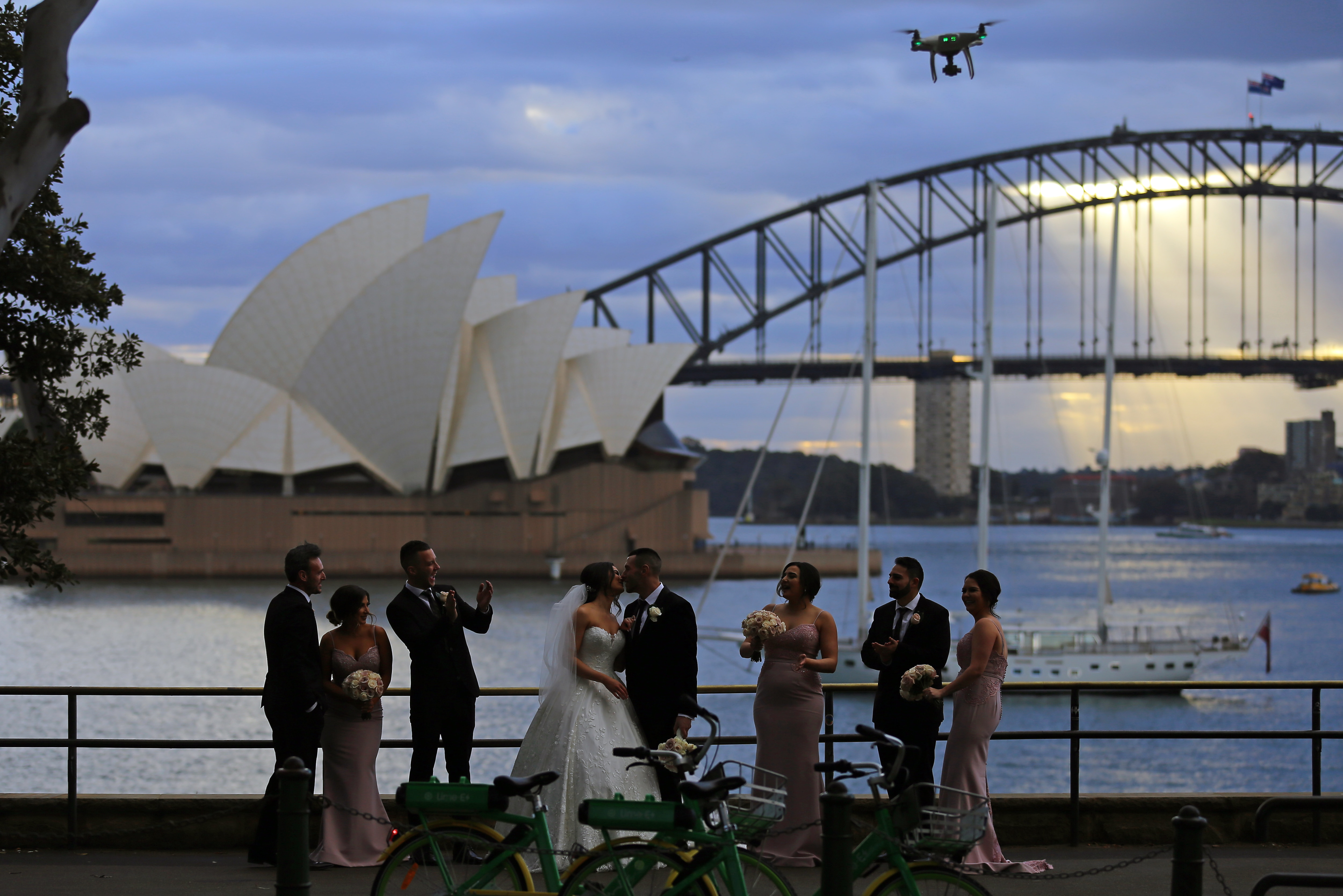 The Sydney Harbour Bridge and the Sydney Opera House are seen as a wedding party takes photos during the winter solstice in Sydney, Saturday, June 22, 2019. (AAP Image/Steven Saphore) NO ARCHIVING