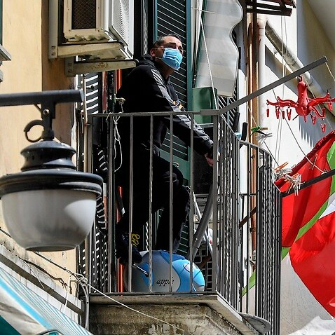 Man wearing a protective mask using his exercise bike out her home balcony, in the Spanish quarter of Naples.