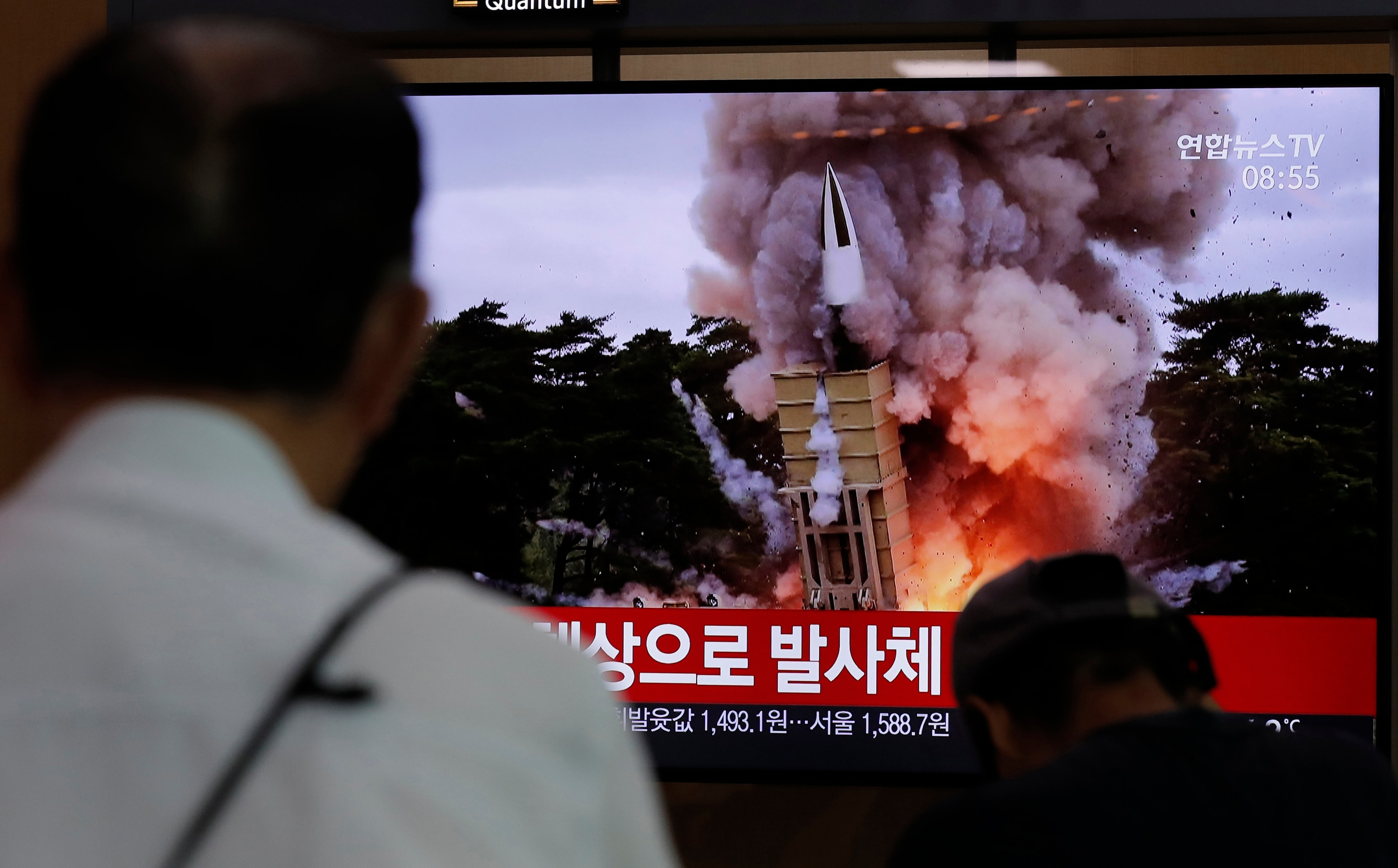 People watch a TV news program reporting about North Korea's firing of projectiles.