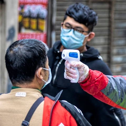 A man measures people's body temperature at a roadblock in Guangzhou, China, 13 February 2020.