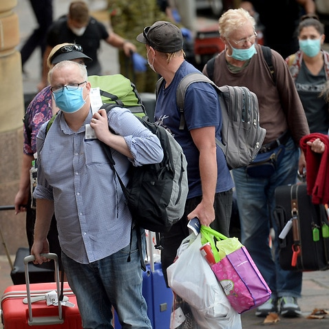 Returning overseas travellers are ushered into the InterContinental Hotel for the beginning of their 14-day imposed quarantine in Sydney, Sunday, March 29, 2020. (AAP Image/Jeremy Piper) NO ARCHIVING