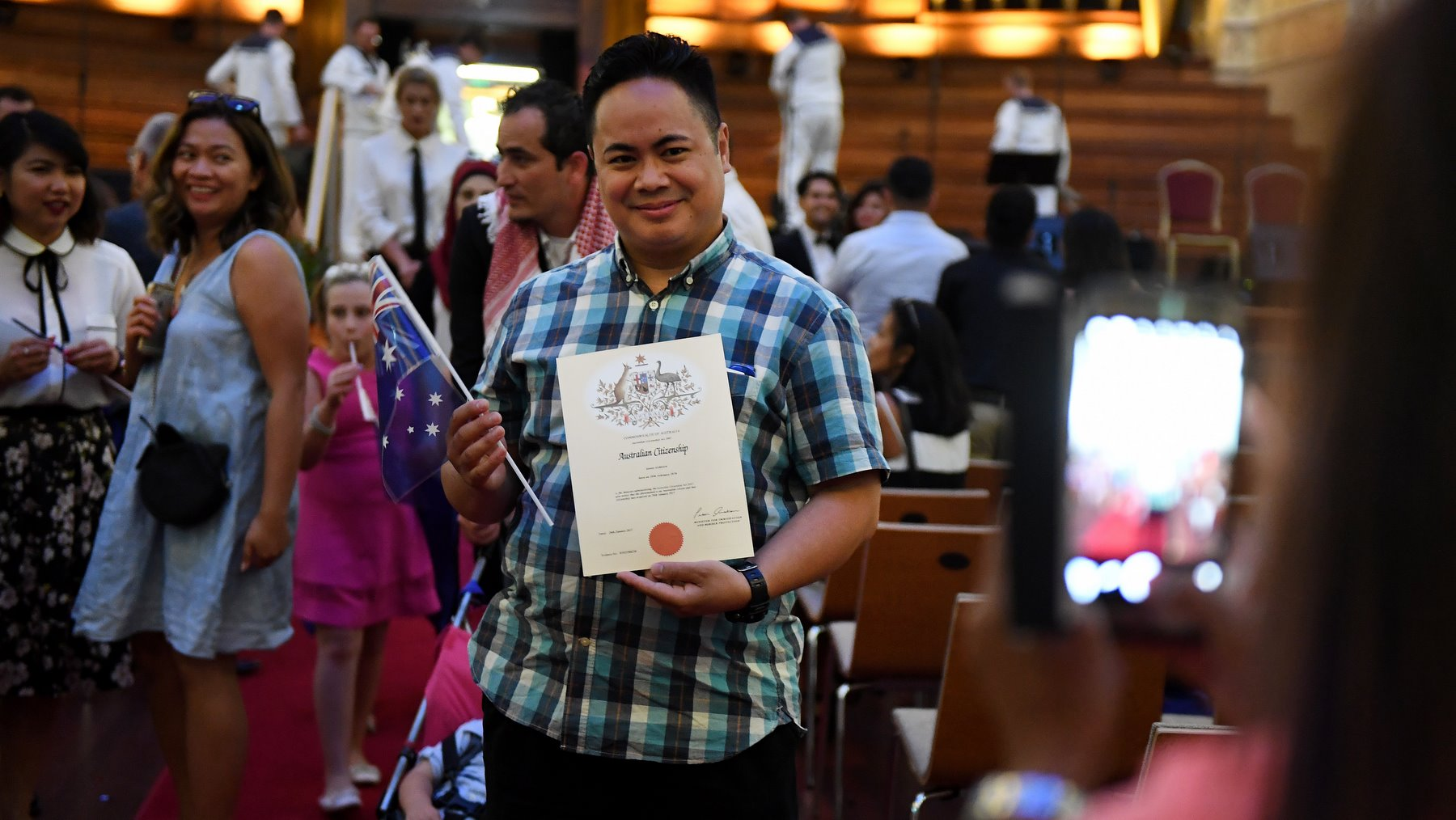 An Australian citizenship recipient poses for a photo after  a citizenship ceremony on Australia Day in Brisbane, Thursday, Jan. 26, 2017. (AAP Image/Dan Peled) NO ARCHIVING