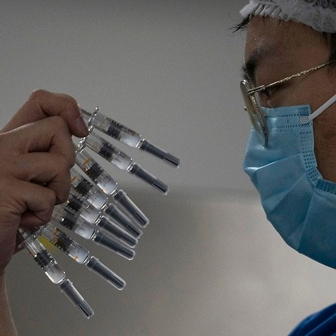 A worker manually inspects syringes of the SARS CoV-2 Vaccine for COVID-19 produced by Sinovac at its factory in Beijing.