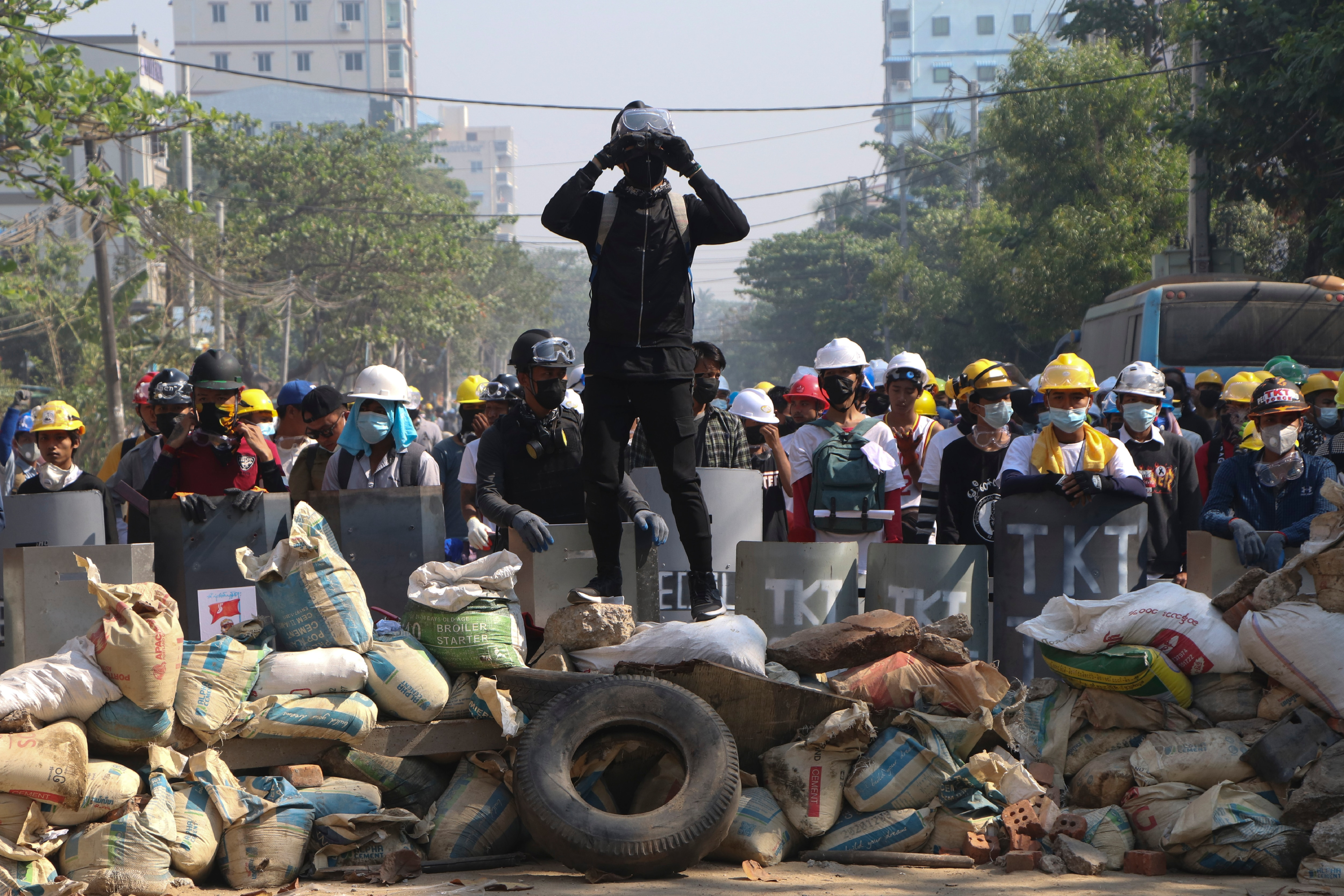 Protesters take positions behind a makeshift barricade in Yangon, Myanmar, Sunday, March 7