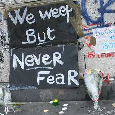 A sign reading We weep but never fear next to flowers and candles are seen at place de la République in Paris