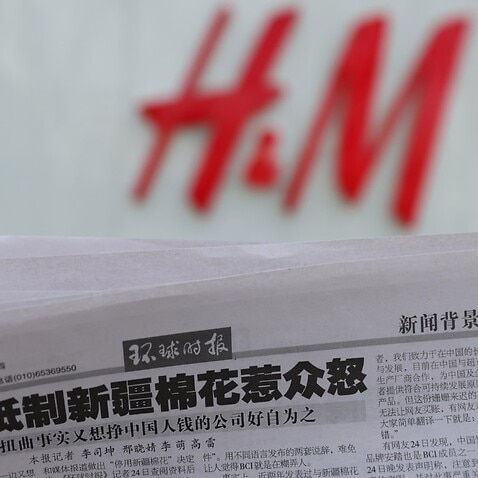 A newspaper with a report about H&M is seen in front of a H&M logo