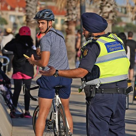 ビクトリア警察の警官が4月にメルボルンのセントキルダビーチで男と話します。
