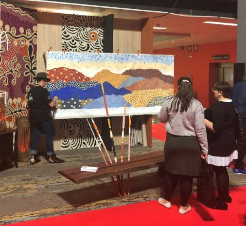 Indigenous artist Danielle Mate Sullivan painting in front of visitors at the furniture fair in Milan.