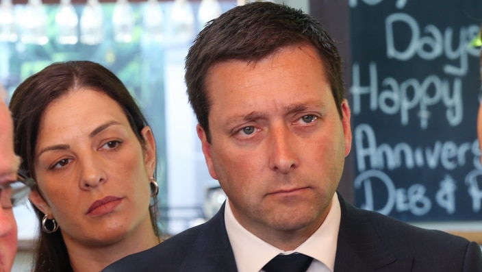 Victorian Leader of the Opposition Matthew Guy speaks to the media while his wife Renae Guy (left) watches on  Monday, November 19, 2018.