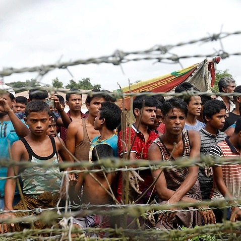 Rohingya refugees gather near a fence at the 'no man's land' zone at the Bangladesh-Myanmar border in Maungdaw district, Rakhine State, 24 August 2018.