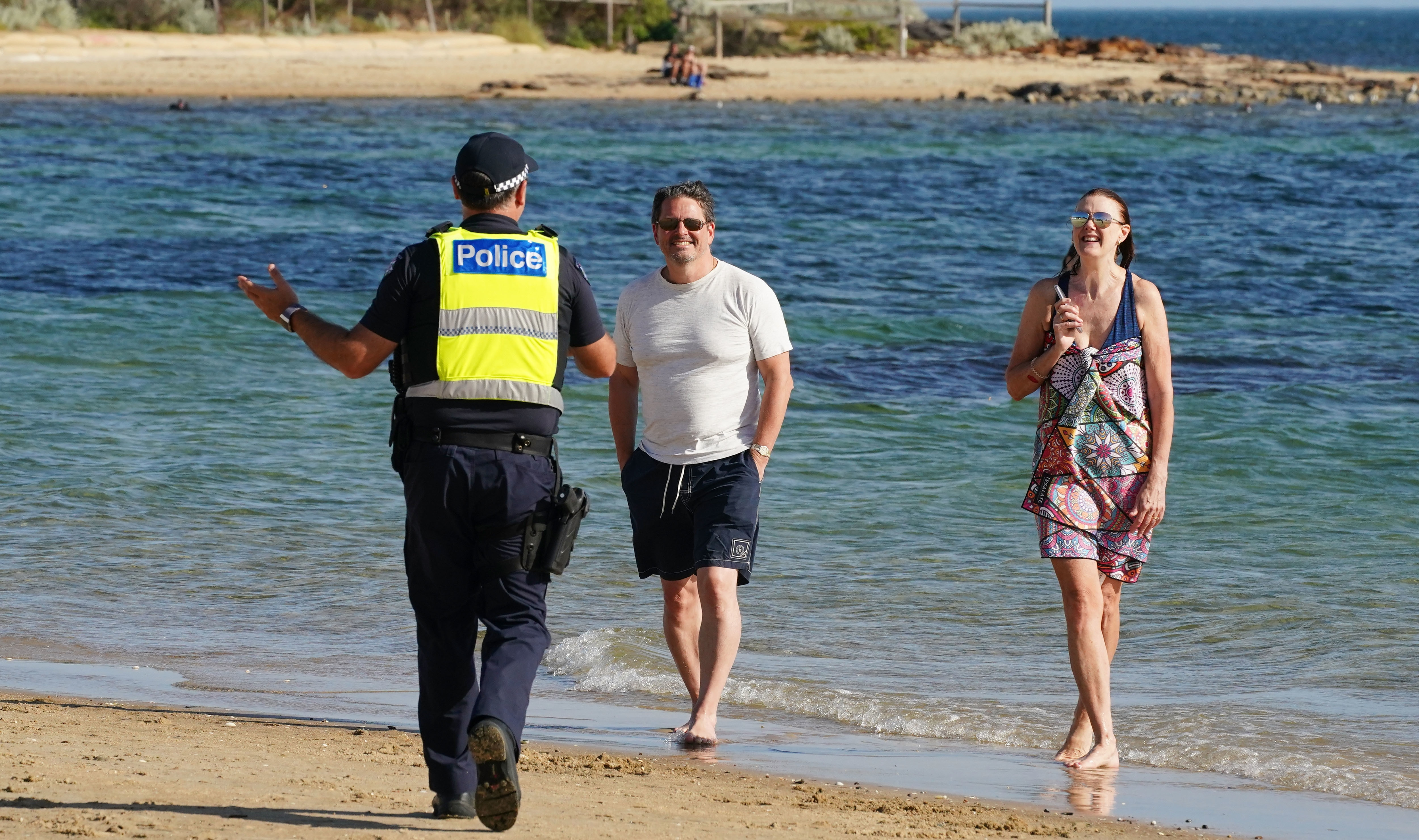 Victoria Police officers ask people to leave Melbourne's Brighton Beach.