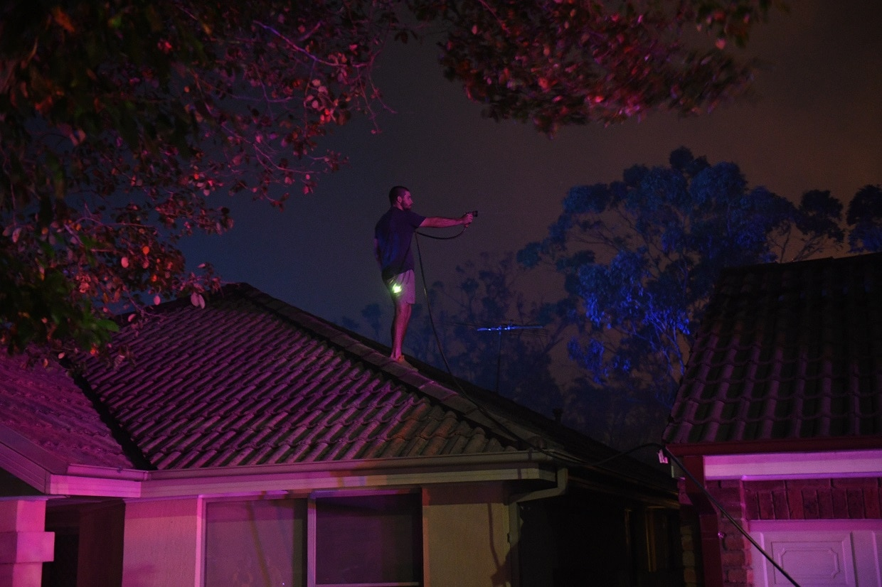 Local resident Jordan Dodin climbs onto a roof to protect the house from fire in Wattle Grove on Saturday night.