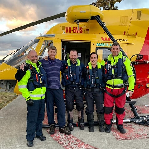 57-year-old bushwalker Michael Bowman (second left) after being rescued from the Lake St Clair region in Tasmania, Tuesday, July 16, 2019.