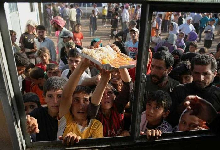 Displaced Iraqis from the Yazidi community gather for food at the Nowruz camp, in Derike, Syria.