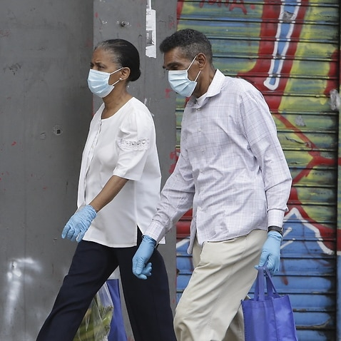 Two people walk wearing masks and gloves in Panama City, Panama, 31 March 2020. Panama accumulates 27 deaths and 1,075 confirmed cases of COVID-19 disease caused by the SARS-CoV-2 coronavirus pandemic.  EPA/Carlos Lemos