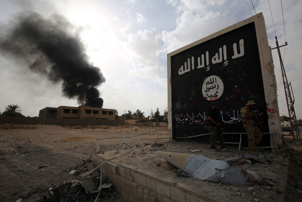 Fighters stand next to a wall bearing the IS group flag as they enter the city of al-Qaim, in Iraq's west