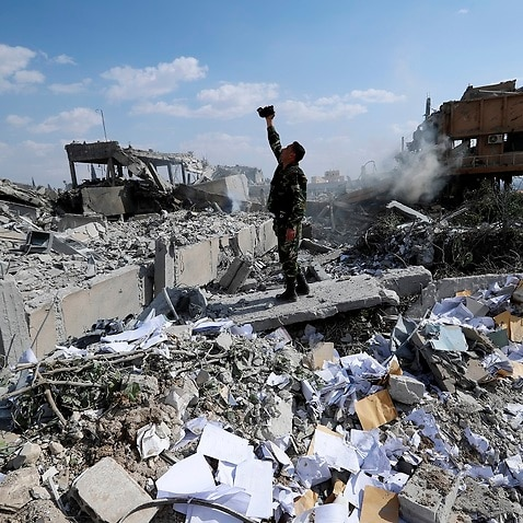 A Syrian soldier films the damage of the Syrian Scientific Research Center which was attacked by US., British and French military strikes.