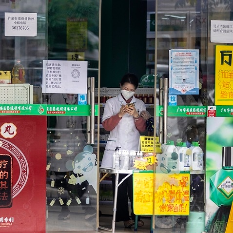 A woman stands in a pharmacy in the Yaotai Community close to African Village in Guangzhou, Guangdong province.