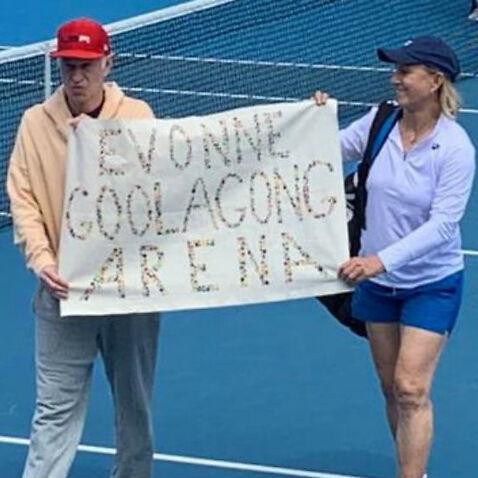 Martina Navratilova and John McEnroe hold up a banner at Margaret Court arena.