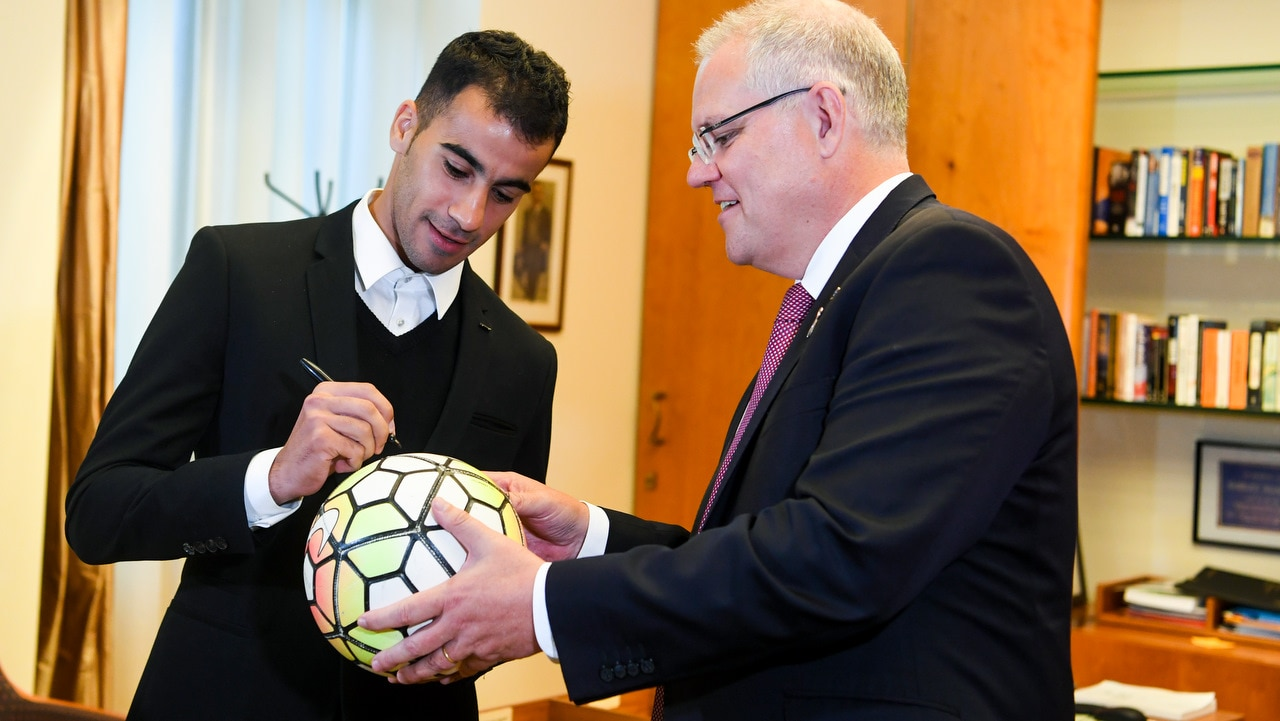 Australian Prime Minister Scott Morrison (right) gets footballer and refugee Hakeem al-Araibi to sign a ball during a meeting at Parliament House.