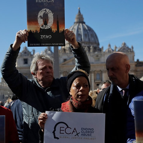 Sex abuse survivors and protestors show banners at the Vatican
