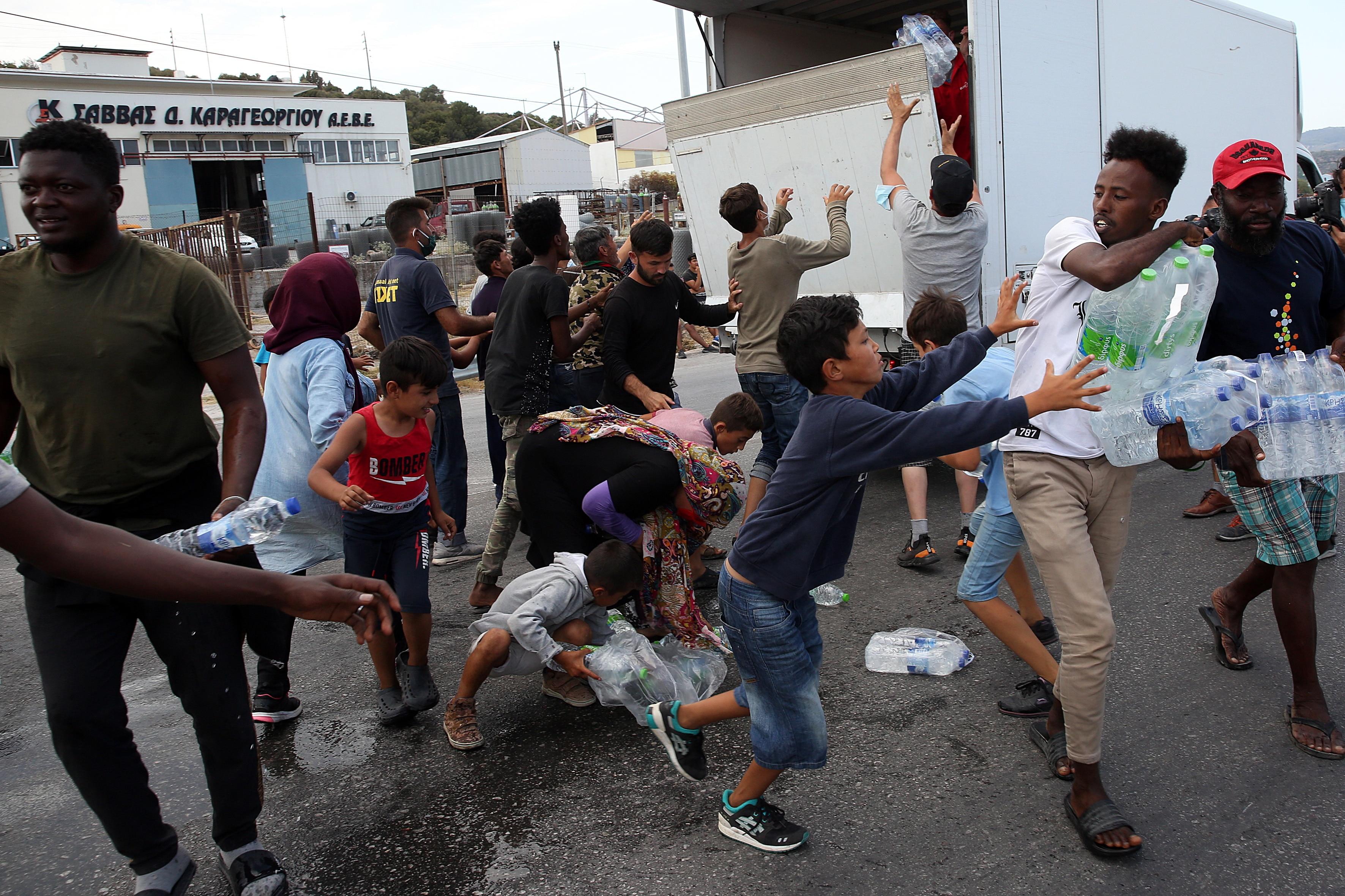 亡命希望者は、9月12日、ギリシャのレスボス島にあるカラテペの新しいキャンプの近くで水を集めるために乱闘します。