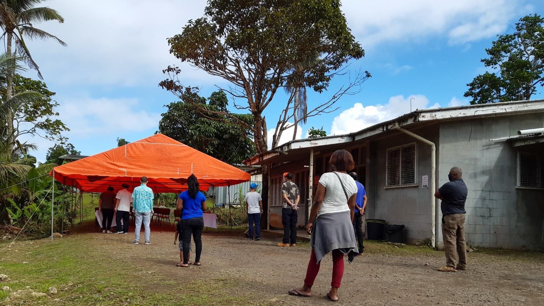 Fiji residents queue outside a COVID-19 vaccination centre in Suva.