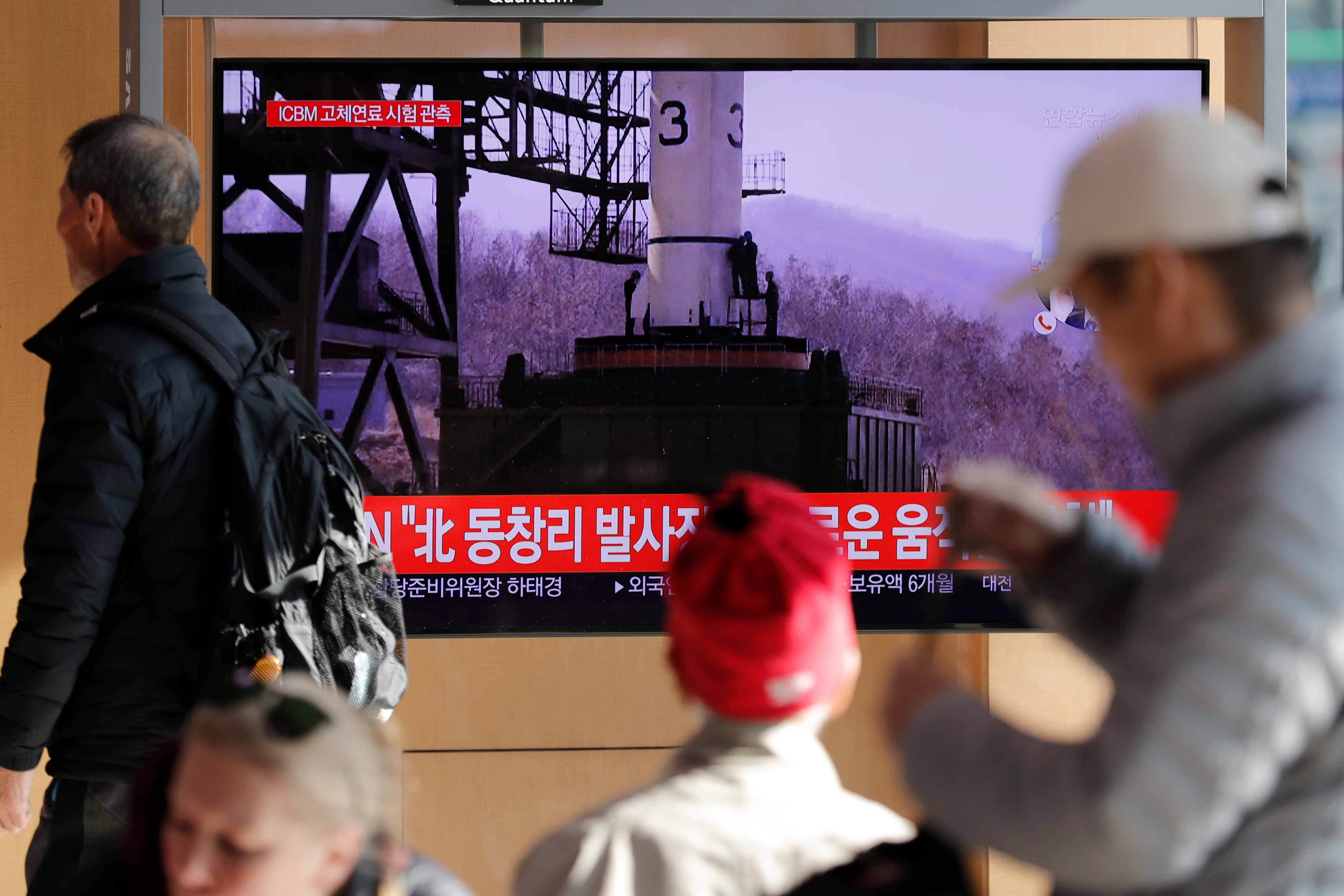 People watch a TV news program reporting North Korea's announcement.
