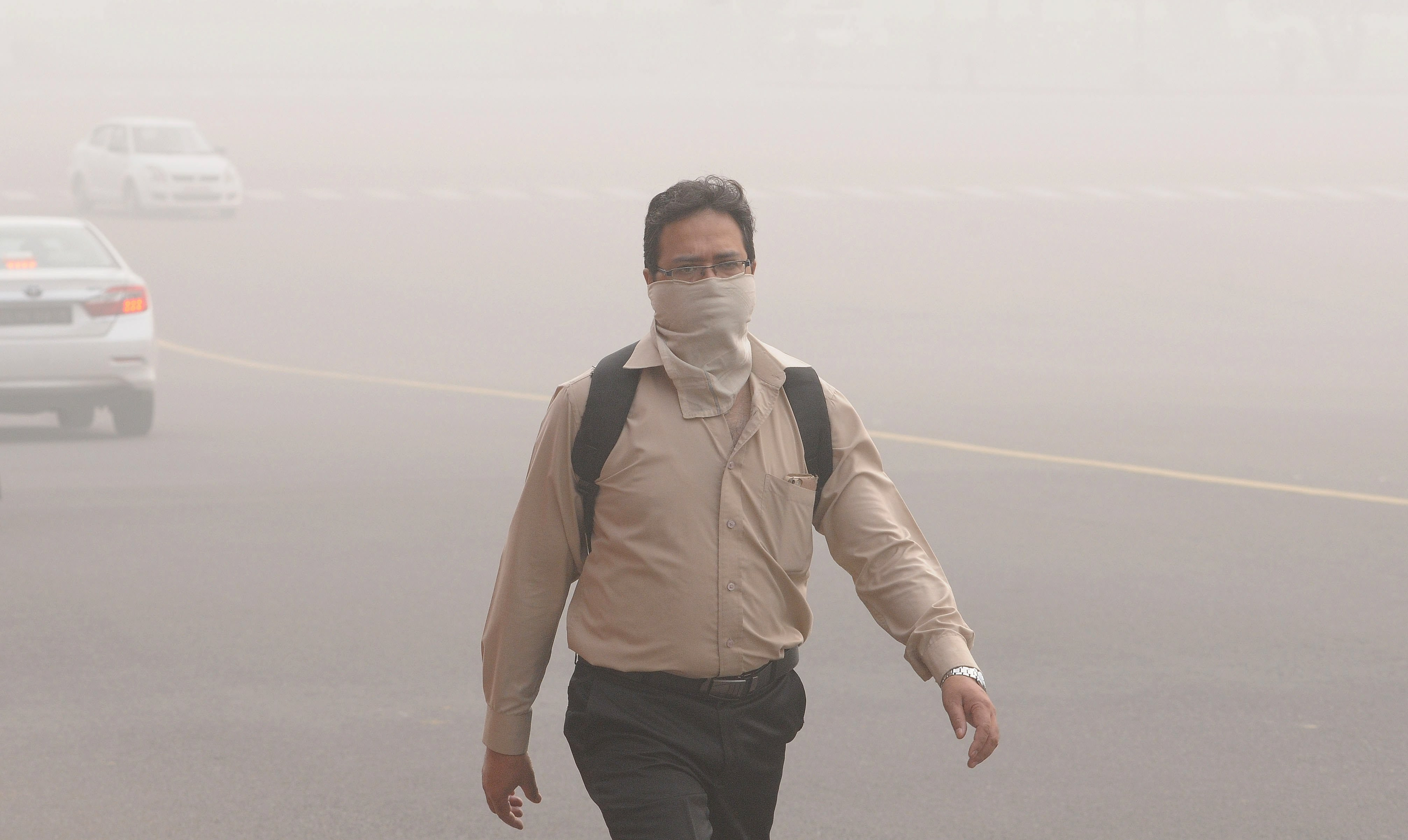 An Indian man with his face covered walks in New Delhi.
