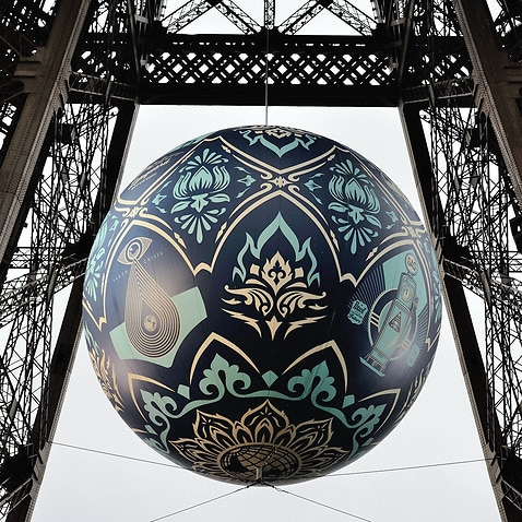 A giant sphere themed on environment hangs between the first and second floor of the Eiffel Tower in Paris