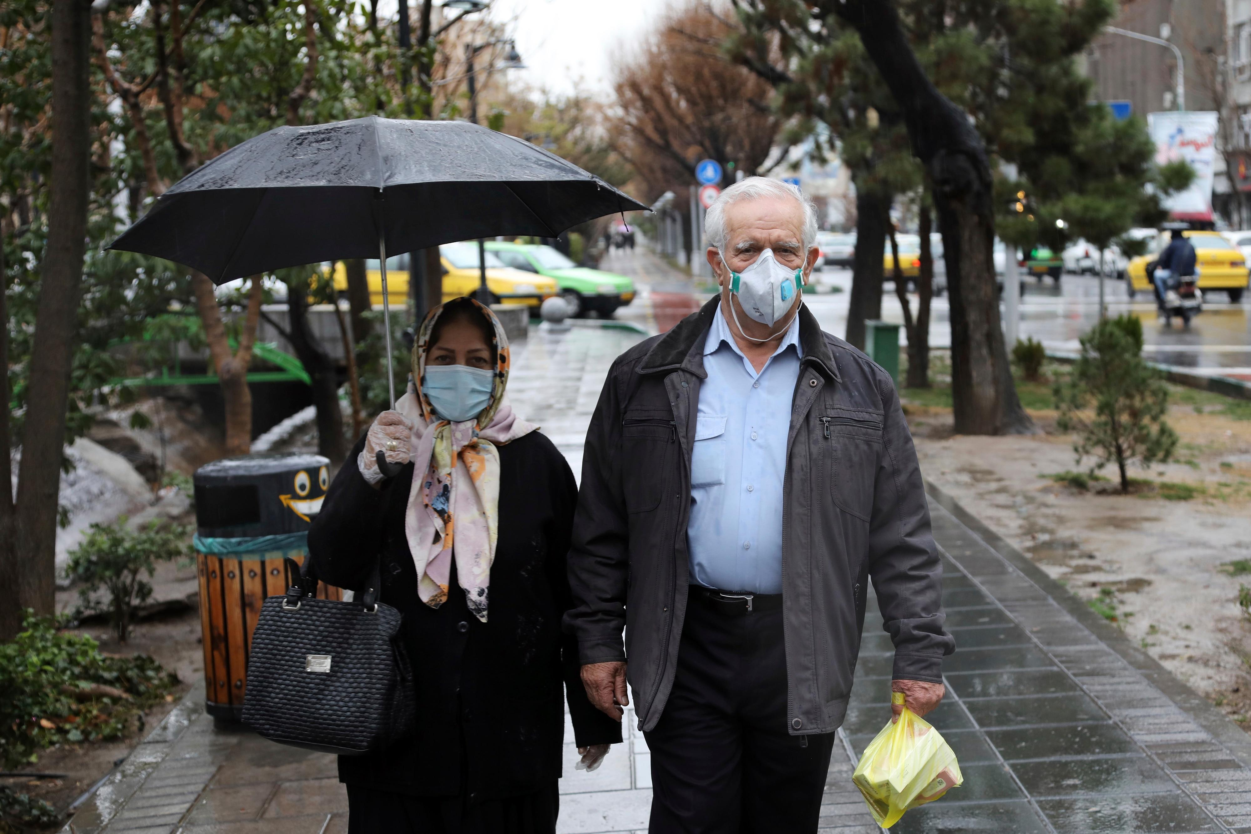 Pedestrians wear masks to help guard against the Coronavirus in downtown Tehran, Iran.