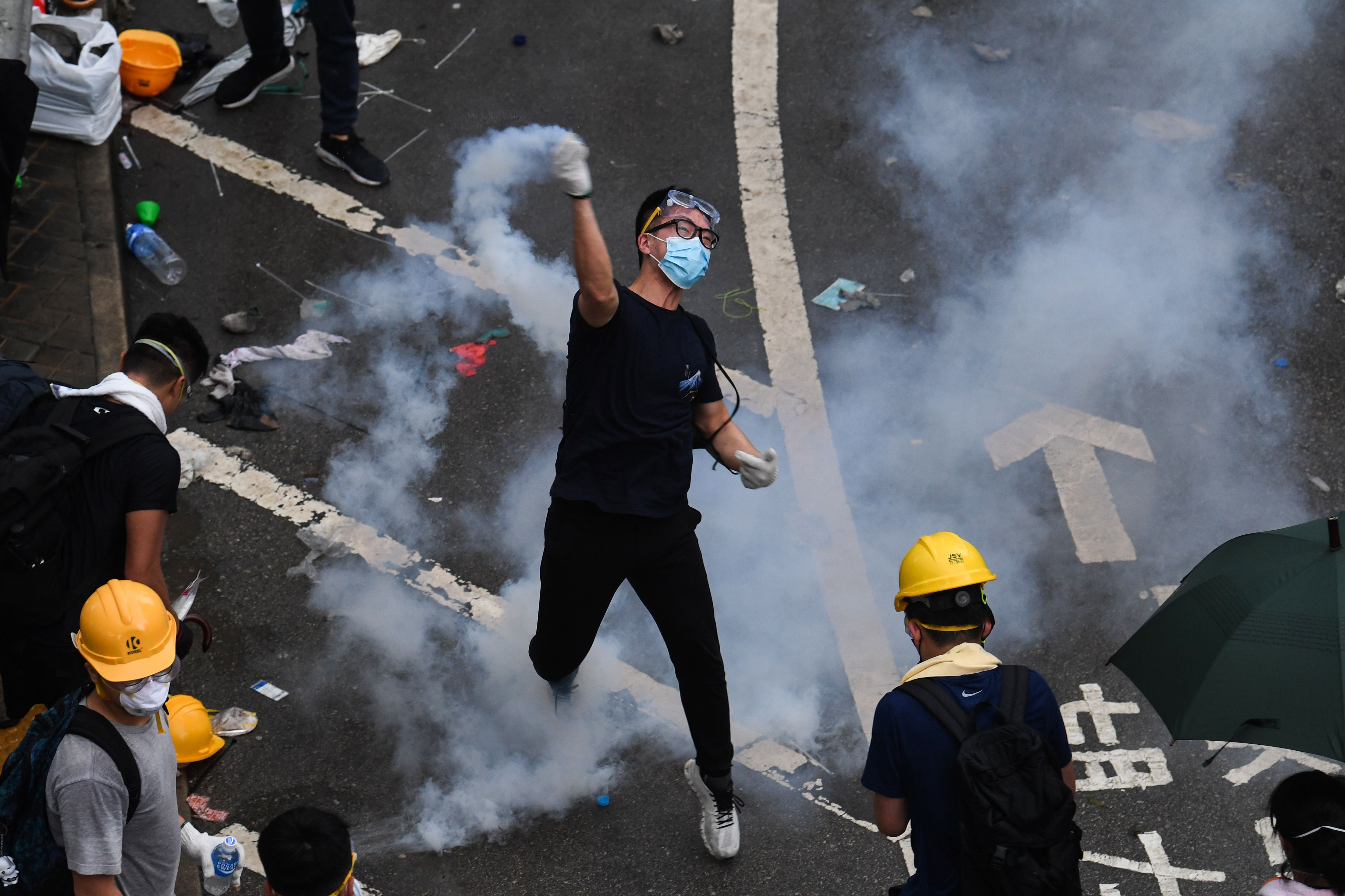 A protester throws back a tear gas during clashes with police outside the government headquarters in Hong Kong on June 12, 2019. - Violent clashes broke out in Hong Kong on June 12 as police tried to stop protesters storming the city's parliament, while t