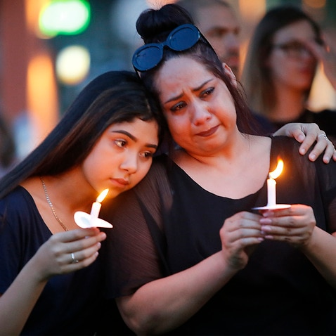 Former El Paso residents Monica Martinez (right) of McKinney and her daughter Tory, 15, during a candle light vigil.