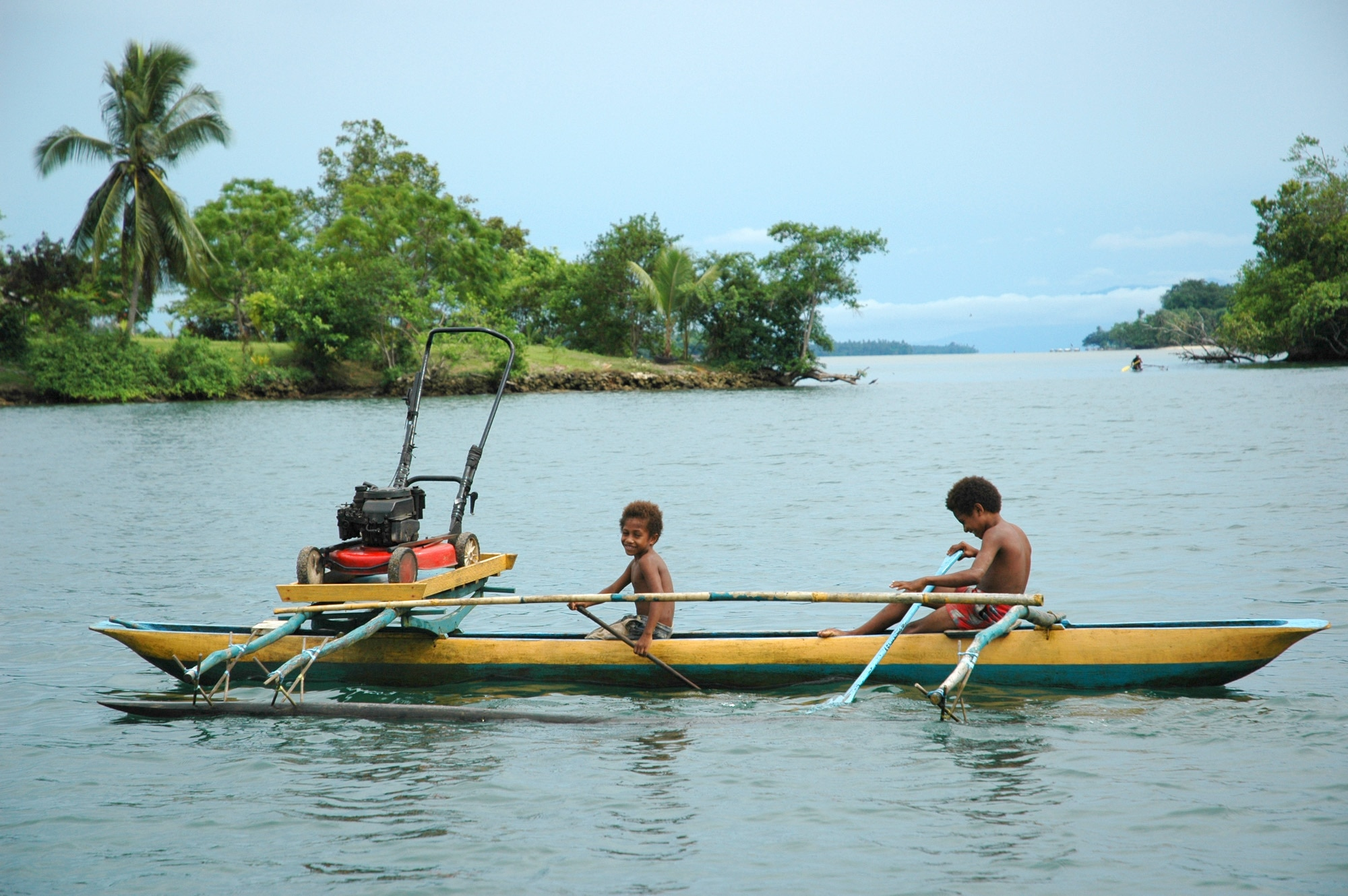 Papua New Guinea: Two boys in an outrigger canoe ferry a lawnmower across a bay near Madang on Papua New Guinea's north coast.