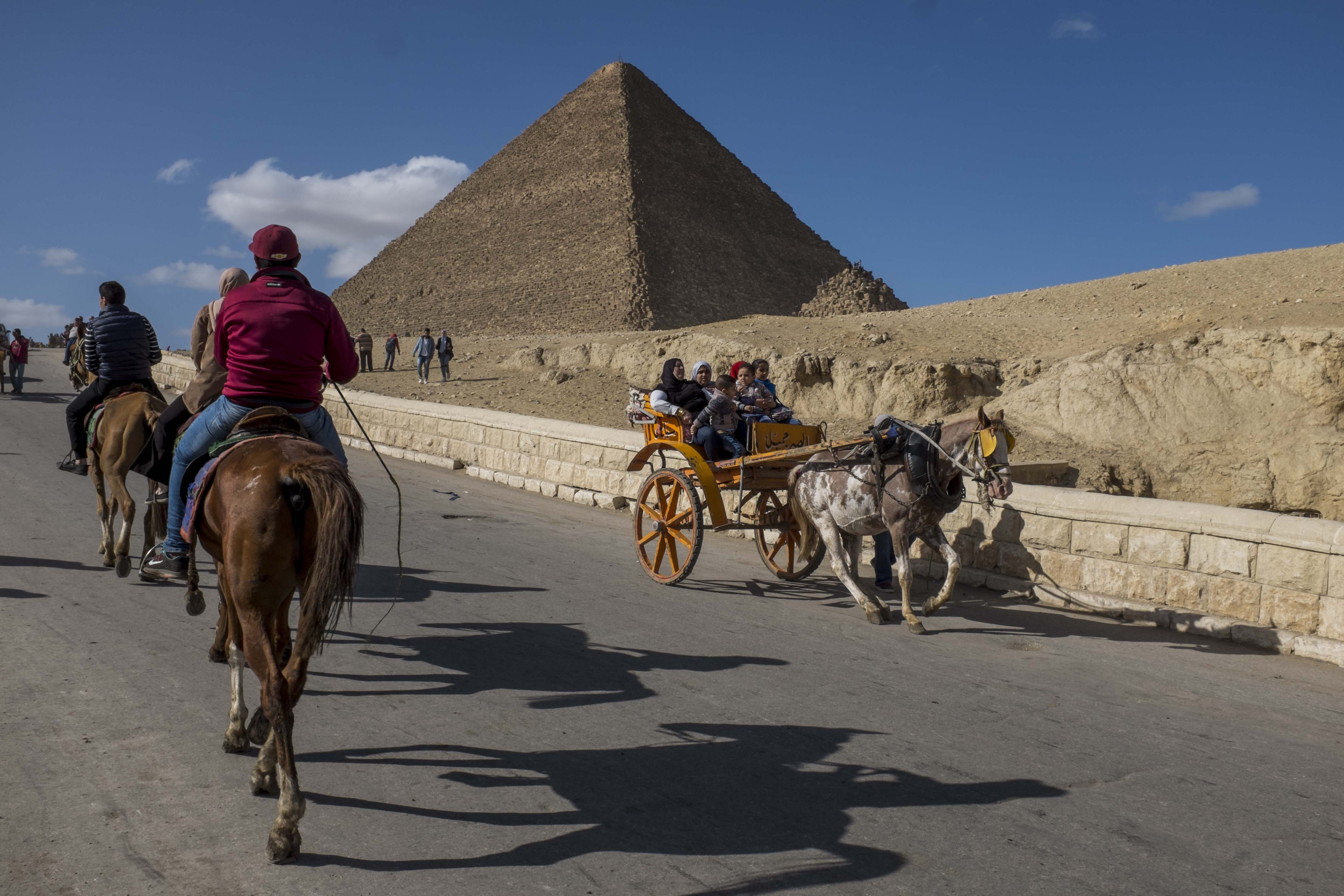 Tourists ride on horses and carriages near the Egyptian pyramids.