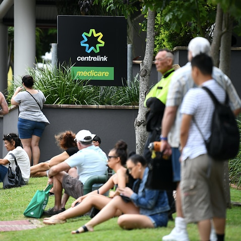 People are seen in long queues outside a Centrelink office on the Gold Coast.