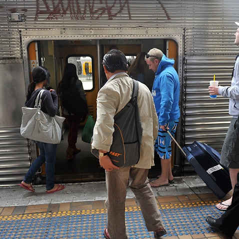 Commuters board a train at a station in Sydney